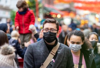 Photograph of two people walking against crowd with face masks on