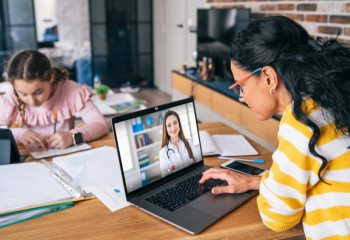 Mother speaking to doctor via Telehealth